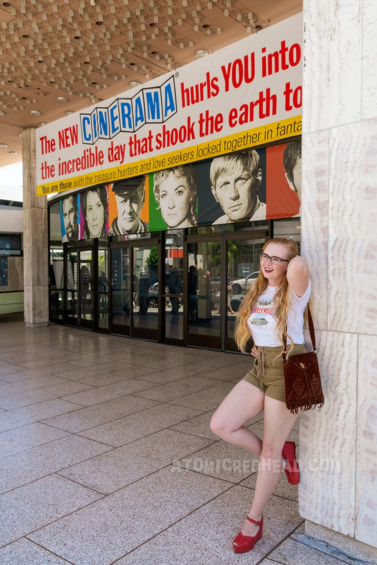 """Myself, wearing a white t-shirt reading """"Hollywood"""" in red letters, and images of the Hollywood Bowl, Farmer's Market, Grauman's Chinese Theater, and the Capitol Records Building, and tan lace up shorts, leaning against a white marble post near the front of the theatre."""