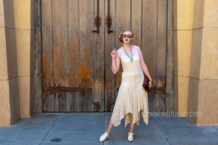 Myself standing in front of a massive pair of wood doors, wearing a sleeveless cream lace dress, a blue scarf with white hieroglyphs, and a blue scarab necklace.