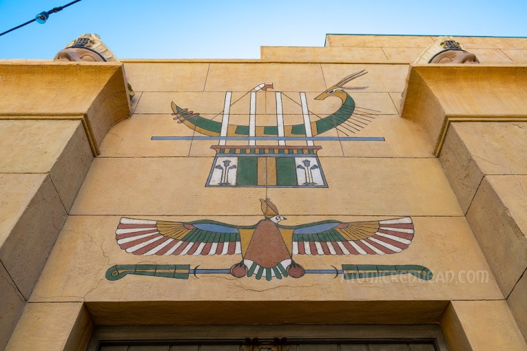 A mural of a hawk and a boat above the pair of wooden doors.