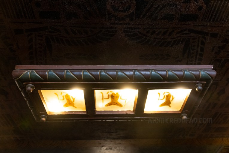A three panel light figure features hieroglyphs.