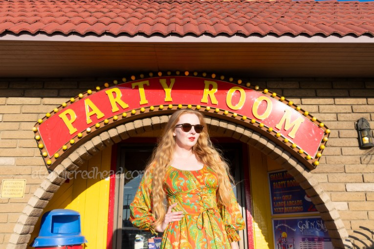 "Myself, wearing a long sleeve, mini dress of orange, yellow, and green in a paisley print, standing in front of the doors to the ""party room."" A garish red sig with yellow letters reads ""Party Room"" with yellow bulbs around the edge."