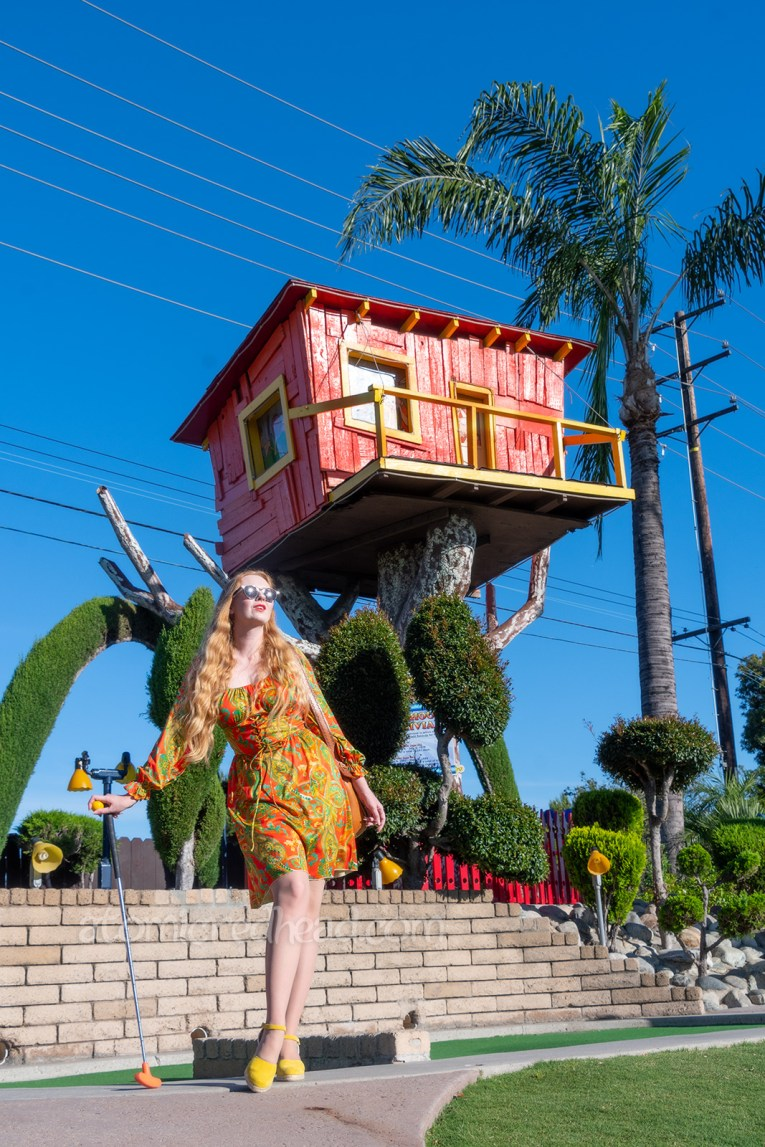 Myself, wearing a long sleeve, mini dress of orange, yellow, and green in a paisley print, standing in front of a tree house.