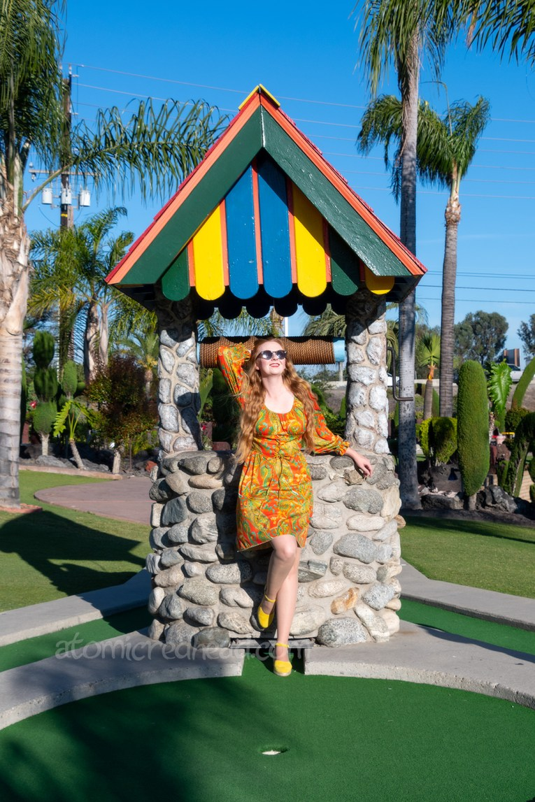 Myself, wearing a long sleeve, mini dress of orange, yellow, and green in a paisley print, standing in front of a well with a bright, multi-colored roof.