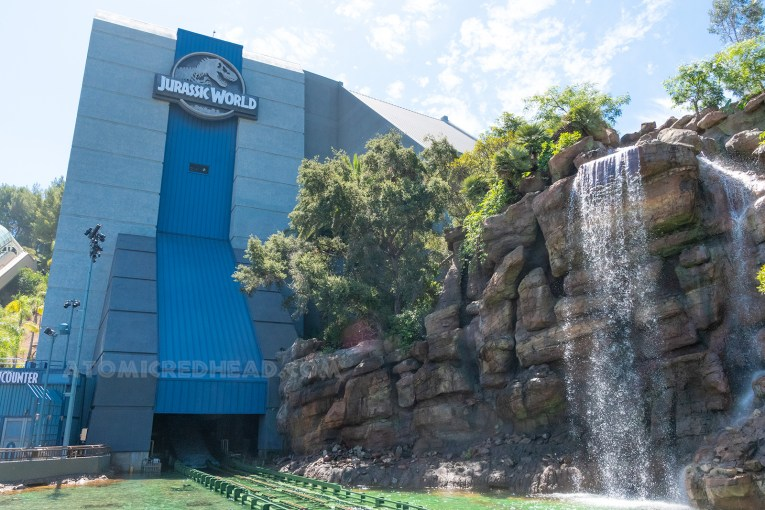 "The Jurassic World ride building, which is painted grey and blue, and features a waterfall in front. The Jurassic World log of the T-rex skeleton and letters reading ""Jurassic World"" is on the top of the building."