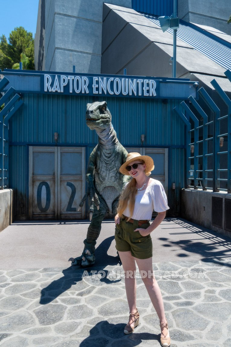 "The raptor known as ""Blue"" for her blue stripe down her side stands outside the Jurassic World ride for Guests to take photos with, I stand in front of her, wearing a straw hat, white peasant top, and olive green shorts."