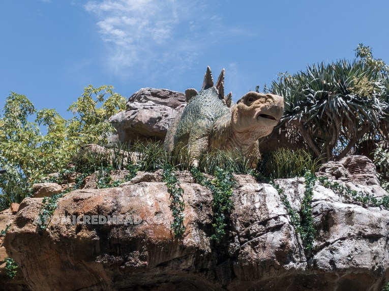 A small stegosaurus stands atop a rock formation.