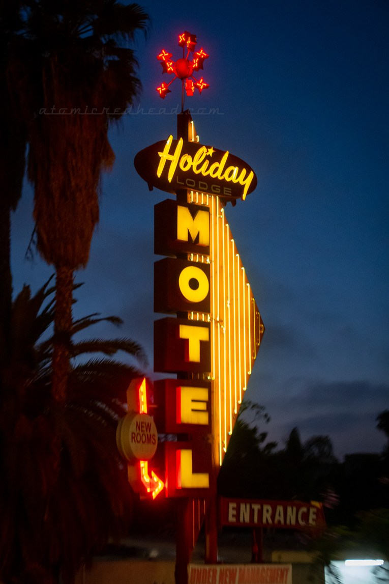 "A sign that combines neon and backlit plastic reads ""Holiday Lodge Motel"" in yellow letters. A starburst creation tops it with red neon stars."