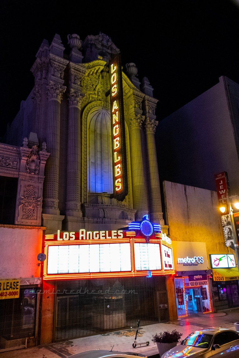 "A Greek revival style building features a tall yellow neon sign reading ""Los Angeles"" and meets a marquee at the bottom also reading ""Los Angeles"" in yellow neon. The marquee is framed in red neon."