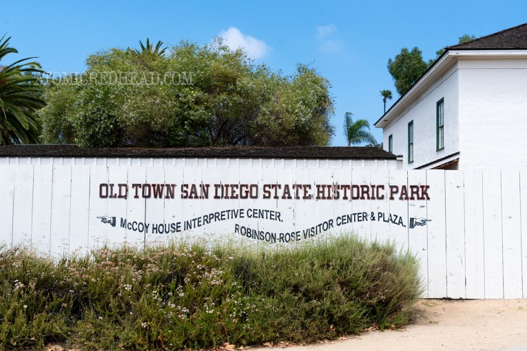 "A white fence with black text reads ""Old Town San Diego State Historic Park"" below in wavy black letters and painted hands pointing reads ""McCoy House Interpretive Center"" one way and ""Robinson Rose Visitor Center & Plaza"" the other way."