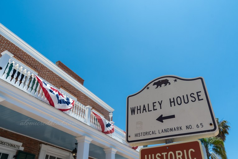 "A brick house with white painted porch sits behind a sign reading ""Whaley House Historic Landmark No. 65"""