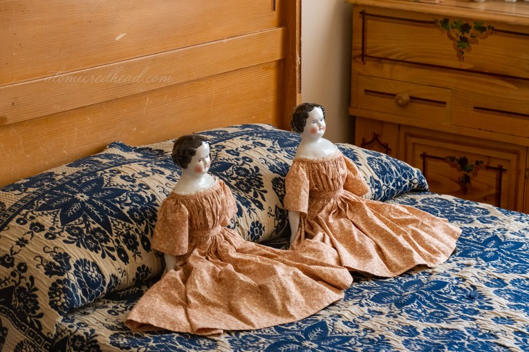 Two porcelain dolls with cloth dresses sit upon a blue and white bedspread in what was one of the children's rooms.