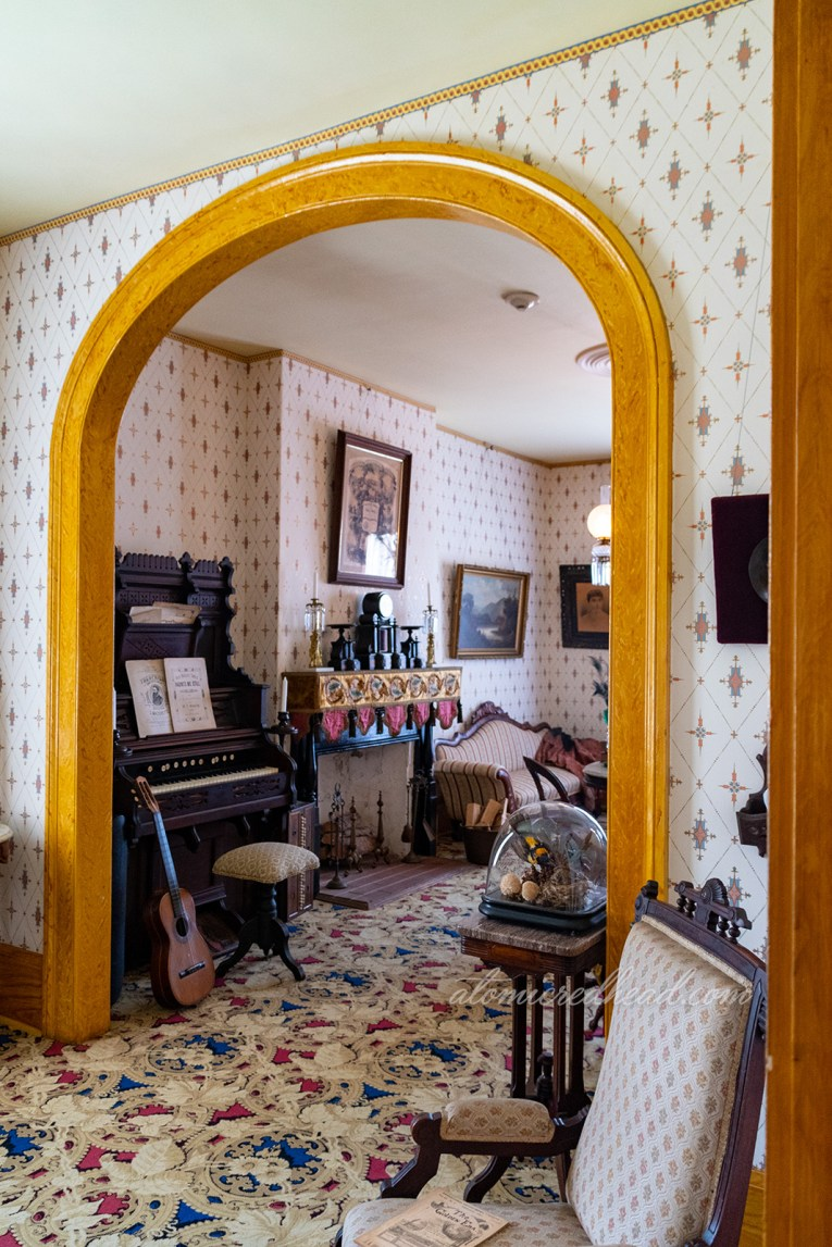 The parlor of the home, with an archway separating two areas. White and gold wallpaper line the walls, a dark wood organ sits agains the wall with a guitar leaning against it, the fireplace is next to it.