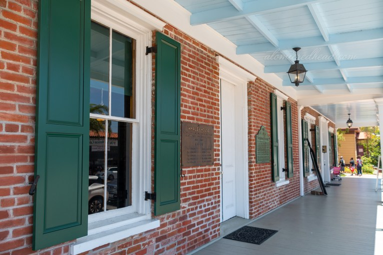 The porch of the home, which is brick, with green shutters.