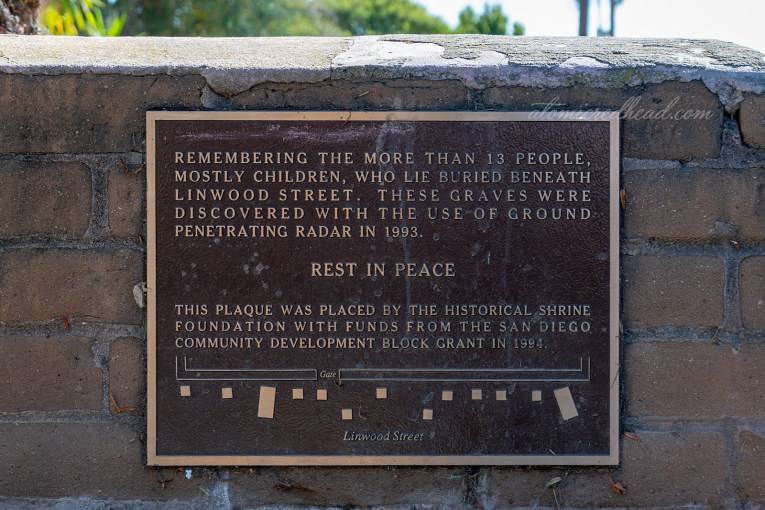 "A bronze plaque reads ""Remembering the more than 13 people, mostly children, who lie buried beneath Linwood Street. These graves were discovered with the use of ground penetrating radar in 1993. Rest in Peace. This plaque was placed by the Historical Shire Foundation with funds from the San Diego Community Development Block Grant in 1994."" A small diagram shows where the graves are in relation to the street and gate to the cemetery."