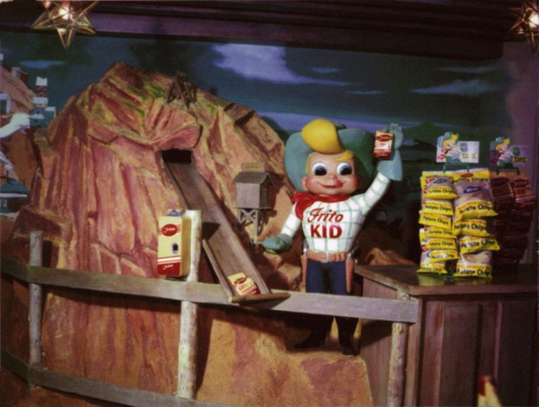 "A large, cartoon looking cowboy in a blue hat atop blonde hair, wearing a red bandana around his neck, a white shirt with blue plaid and red text reading ""Frito Kid"" holding a bag of Fritos stands next to a mountain with a long slide coming from the top."