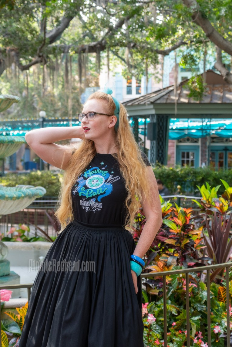 "Myself standing in front of a fountain surrounded by trees dripping in Spanish moss, wearing a black t-shirt with Madam Leota (a medium with her head floating in a crystal ball) and music instruments floating about on it, reading ""Having a Ball"" and a black full skirt."