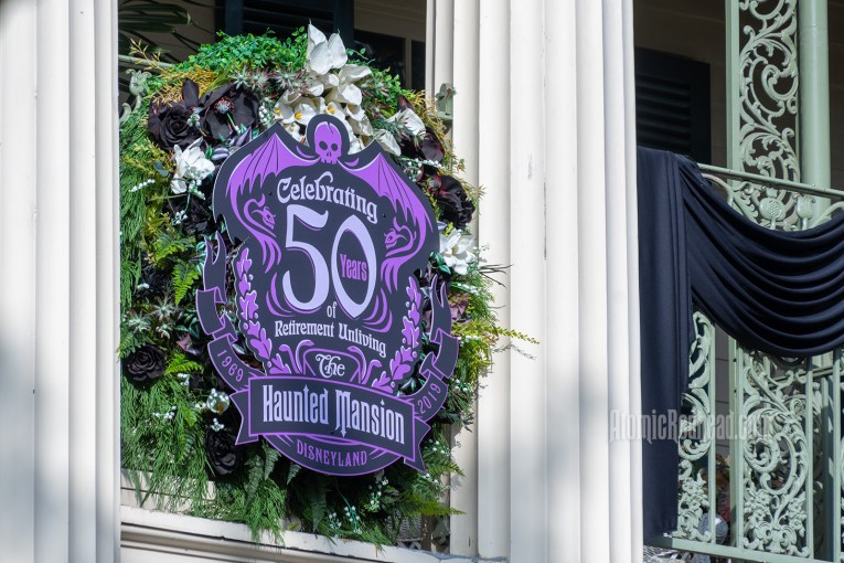 "A purple and black sign hangs on the balcony of the Haunted Mansion reading ""Celebrating 50 years of Retirement Unliving"" The Haunted Mansion 1969 - 2019"
