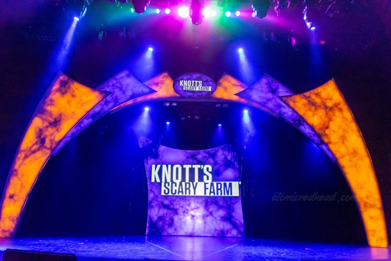 """The stage for the announcement for Knott's Scary Farm, lit in eerie orange and purple lights. Text reading """"Knott's Scary Farm"""" in white letters is on a screen at the back of the stage and a small sig at the top of the stage."""