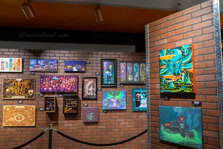 Various works of art depicting Scary Farm monsters hang on a brick wall.