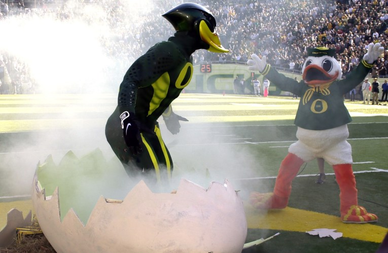 A muscular humanoid duck of green and yellow emerges from a large egg.