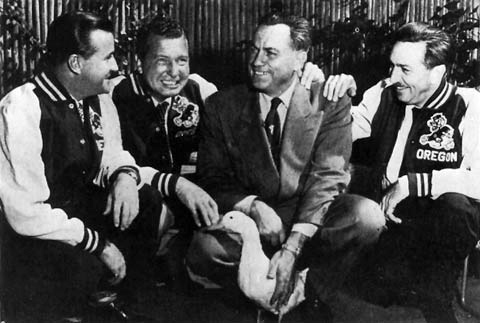 A black and white image of Walt Disney wearing a University of Oregon letterman jacket, along side University officials, and a live white duck.