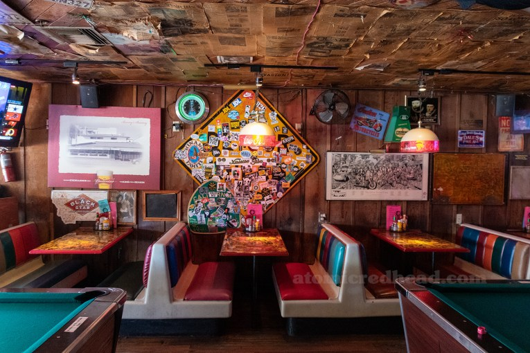 Interior of Barney's, newspapers cover the ceiling, artwork, signs, and other odds and ends hang from wood paneled walls. Multi color booths sit against the wall, pool tables are just off frame.