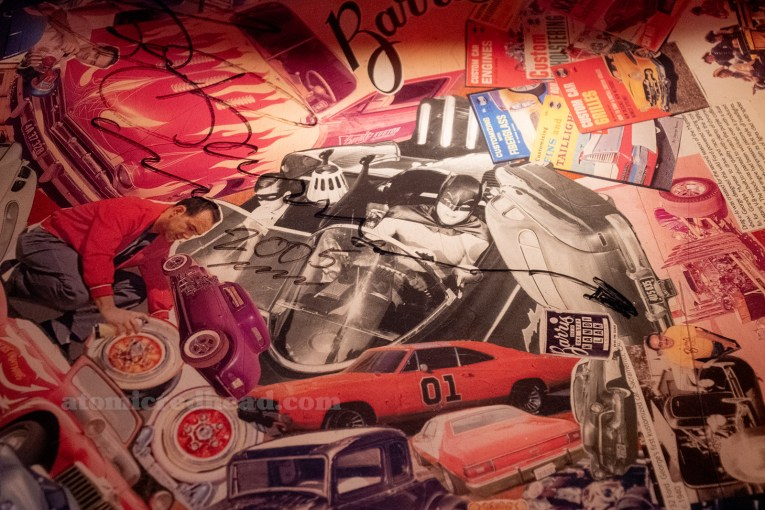 Close-up of one of the table collages that feature the cars of George Barris, and is signed by him.