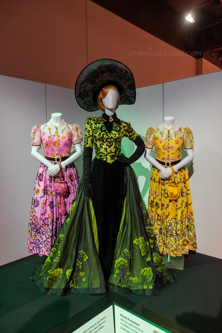 The stepmother and stepsister costumes from the live action Cinderella. The stepmother wears a vibrant green and black ensemble with large black hat. The stepsisters wear matching floral embroidered dresses, however one is pink, the other is yellow.