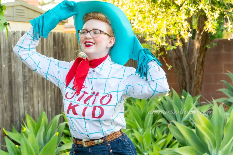 "Myself standing in our backyard, with lush agave plants, wearing a blue cowboy hat, blue gloves, red bandana, a white shirt with blue plaid and red text reading ""Frito Kid"" and blue jeans, and brown cowboy boots."