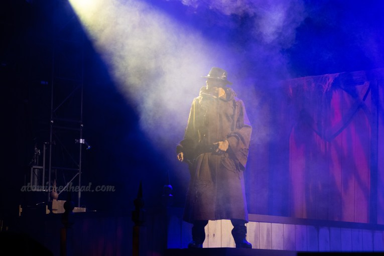 A cowboy stands in a spotlight on the stage for The Hanging.