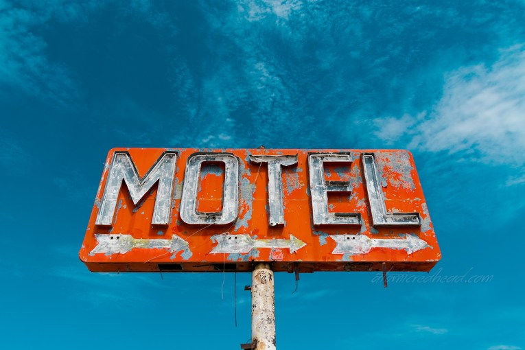 "A red sign with flaking paint reads ""Motel"" in broken neon. Three small arrows point to the right."