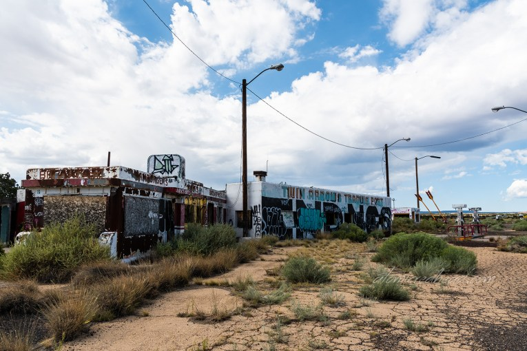 The shell of the Twin Arrows Trading Post and cafe. The exterior is covered in graffiti and all of the windows are broken out. Large bushes have overtaken the ground out front.