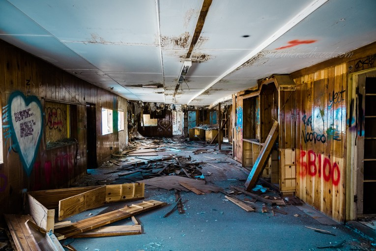 Interior of the Twin Arrows Trading Post. Wood panel walls, which are covered in graffiti line a long room. Debris scatters a blue carpet. Stains appear here and there on the white ceiling.