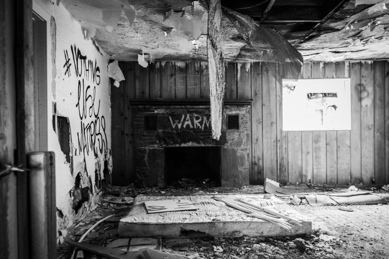 "Interior of the Twin Arrows Trading Post. A black and white photo. The ceiling is peeling away to reveal bare studs. A stone fireplace has had ""WARM"" spray painted on the top of it. A mattress lays on the floor among other bits of debris."