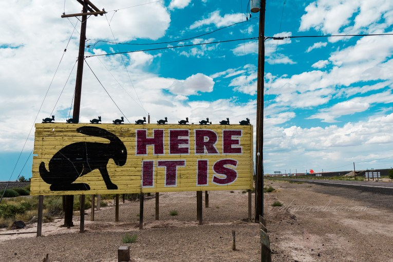 """A large, low billboard is yellow and features a large black jackrabbit, red letters to the right read """"HERE IT IS"""" and small jackrabbits line the top of the billboard."""