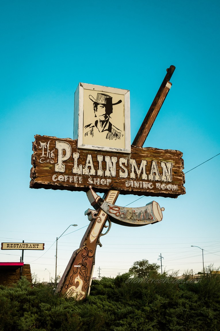 """Sign for the Plainsman Restaurant. A large metal and neon rifle juts up toward the sky. Across the middle of it a faux wood sign reading """"The Plainsman"""" and a framed image of a cowboy is atop it."""