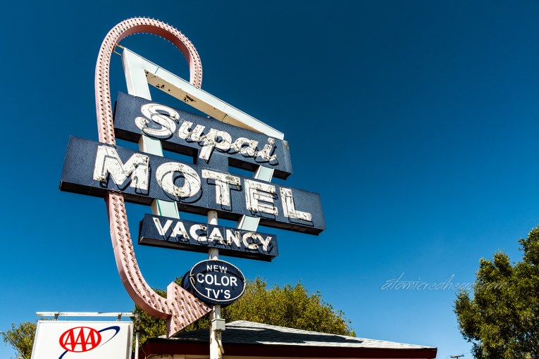 """Faded neon sign for the """"Supai Motel"""" which is made up of blue square and a faded red curling arrow."""