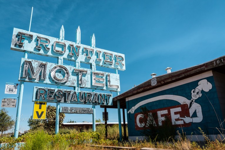 """Faded blue neon sign for the Frontier Motel and Restaurant. A mural painted on the side of the building features a chef and the word """"Cafe"""""""