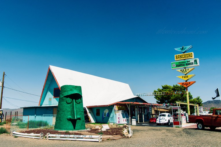 """A blue A-frame building sits with a white roof. A massive green tiki heads sits out front. A colorful sign reads """"Antares Point Ranchero Home of Giganticus Headicus"""""""