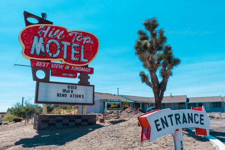 "Sign for the Hill Top Motel which is red and made of metal and neon. A white arrow edged in red reads ""Entrance"""