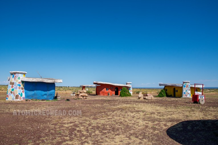 The residential area of Bedrock city, three concrete structures, flat roofs, that appear to be made of stone, one blue, one orange, one yellow.