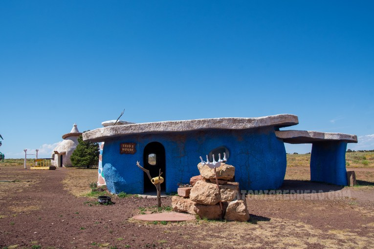 Fred Flintstone's house, which is painted blue, and is made to look like it is made of one giant rock, but is really made of concrete and features a flat slab like roof.