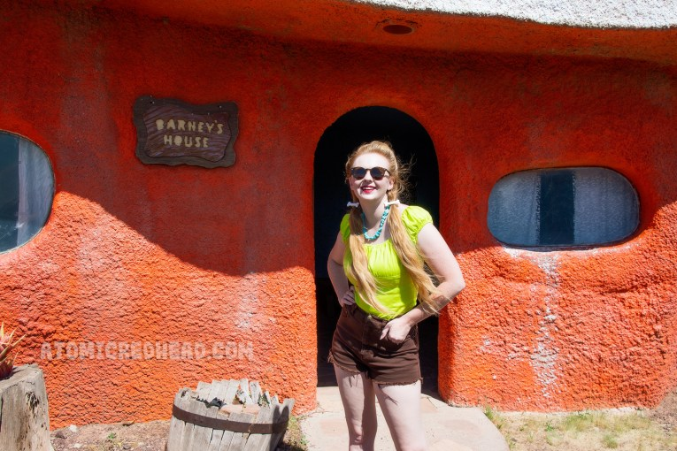 Myself, wearing a lime green peasant top, brown cut off jean shorts, and my hair in pigtails with small bone clips in my hair. Behind me, an orange concrete structure that looks like a caveman's home.