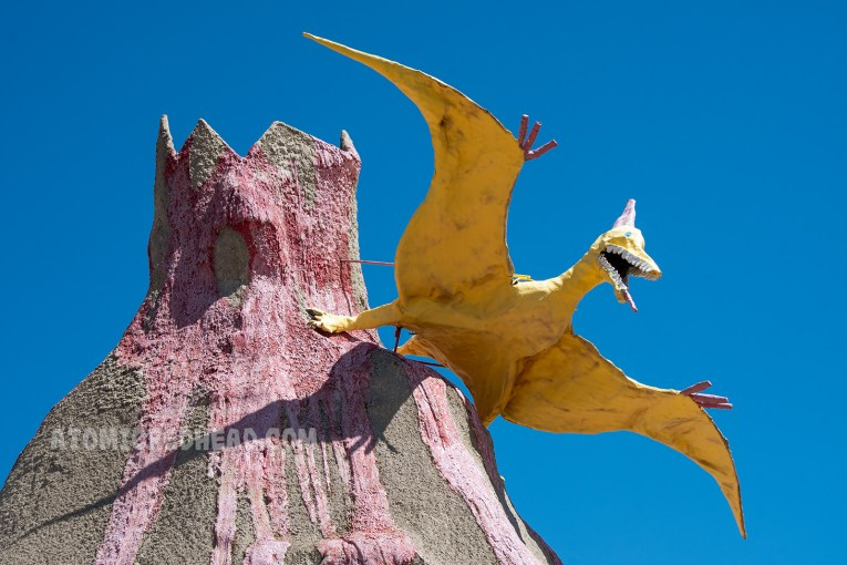 A yellow pterodactyl appears to be flying over a giant volcano.