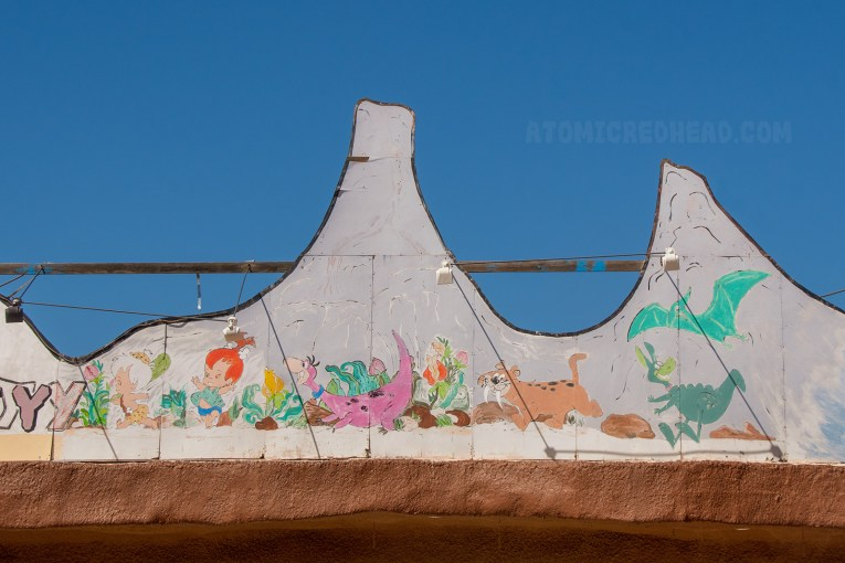 Part of the massive sign features a mural of various dinosaurs and Pebbles crawling.