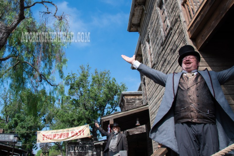 The Deputy Mayor welcomes Guests to the town, wearing a grey suit with gold brocade vest and top hat. His arms outstretched in welcome. Behind him a street of old west buildings and a banner reading 'Founder's Day'
