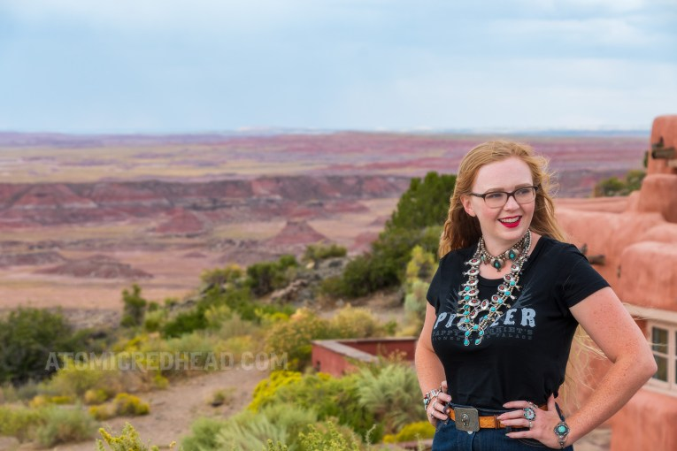 "Myself, wearing several turquoise and silver necklaces, a black t-shirt reading ""Pioneer"" in white letters, and a jean skirt, standing in front of the Painted Desert Inn."