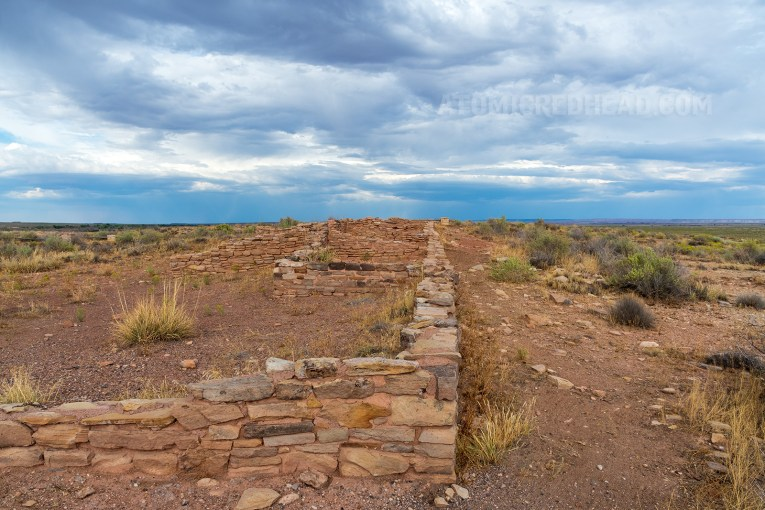 The ruin of an ancient dwelling. Several yellowish tan stones stacked on top of each other to form what is left of a wall.