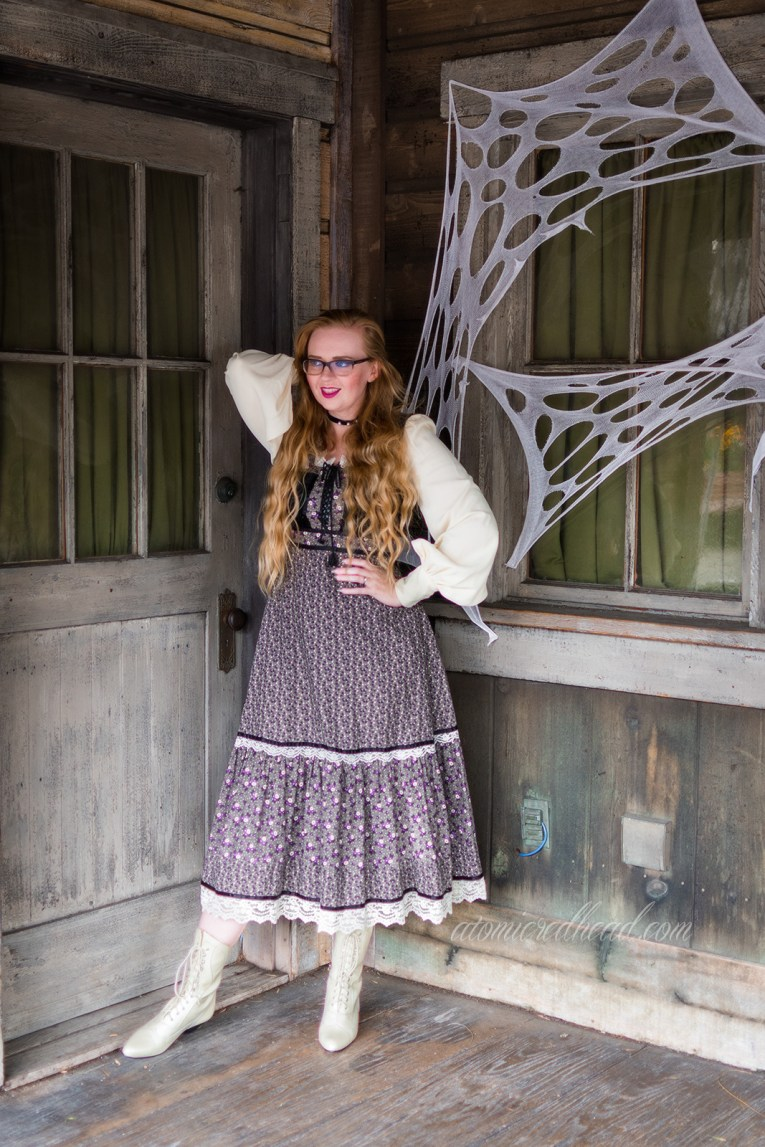Myself, standing in front of a distressed old west wood building, wearing a long, black, white, and grey dress, with a black velvet bodice, and billowy white sleeves.