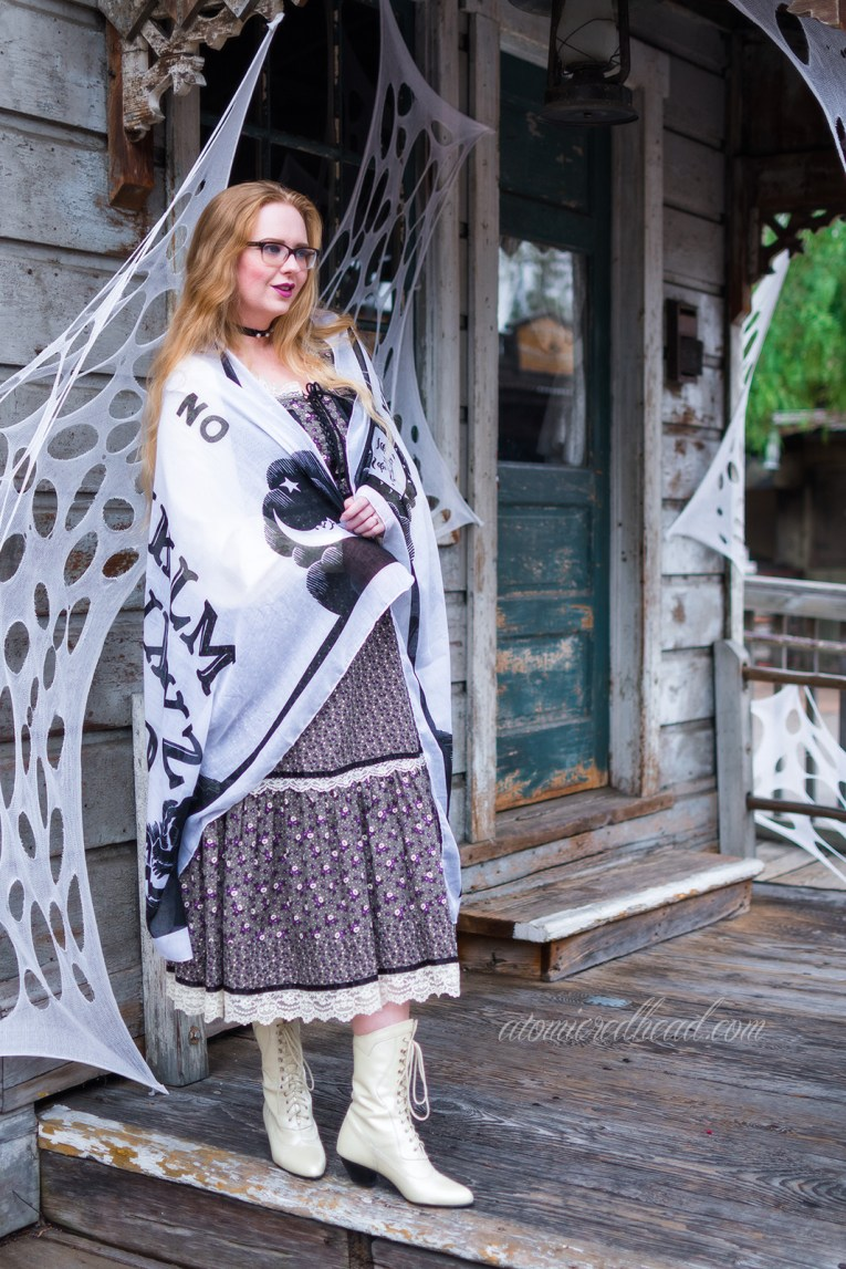Myself, standing on the porch of an old west building, wrapped in a shawl printed with the design of a Ouija board.